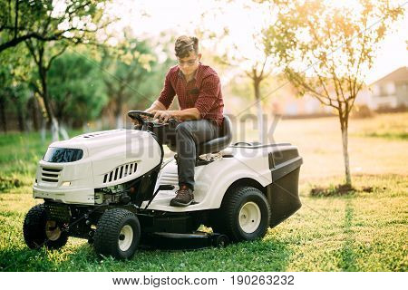 Ride-on Lawnmower Tractor With Worker Doing Landscaping Works At Weekend Sunset