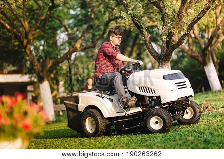 Professional Gardner Using Lawn Mower And Cutting Grass