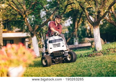 Smiling Handsome Man Using Lawn Mower And Cutting Grass In Home, Residential Garden