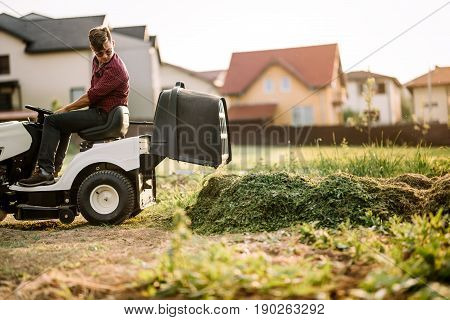 Man Using Lawn Tractor And Cutting Grass In Garden During Weekend Time