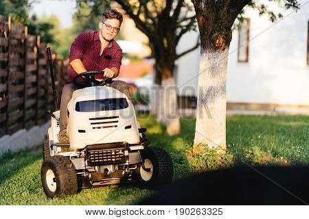 Portrait Of Man Using Lawn Tractor And Cutting Grass In Garden During Weekend Time