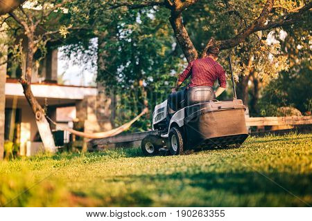 Male Worker Using Professional Lawn Mower For Trimming Backyard Grass. Lansdscaping Works In Progres