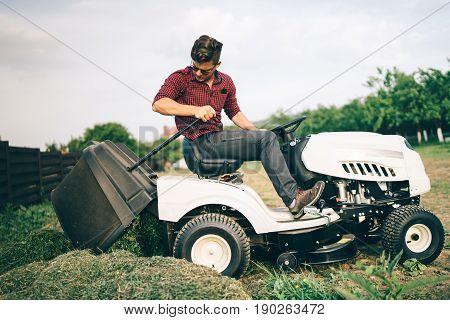 Gardner Doing Landscaping Works And Cutting Grass, Unloading Grass