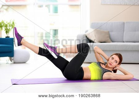 Beautiful woman doing bicycle crunch at home