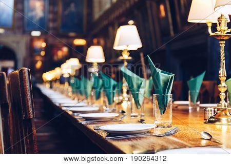 OXFORD, UK - MAY 22, 2017: Table set for a meal at The Great Hall of Christ Church, University of Oxford. The Hall was replicated at film studios as the grand dining hall at Harry Potter's Hogwarts school.