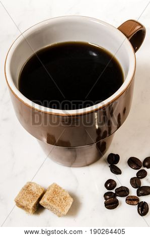 brown cup with black coffee and brown sugar
