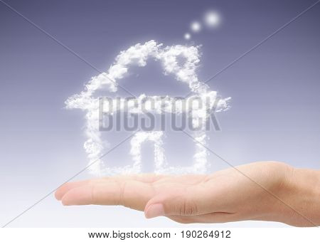 House made from clouds hovering over a hand