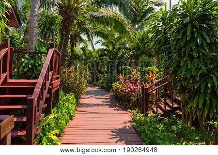 A red boardwalk pathway through a lush green garden