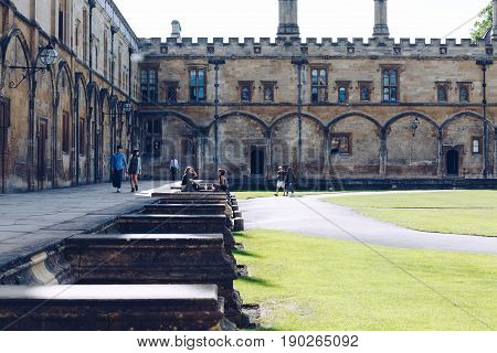 OXFORD, UK - MAY 22, 2017: Students relax in the The Great Quadrangle, or Tom Quad, of Christ Church College, the largest college quad in Oxford.