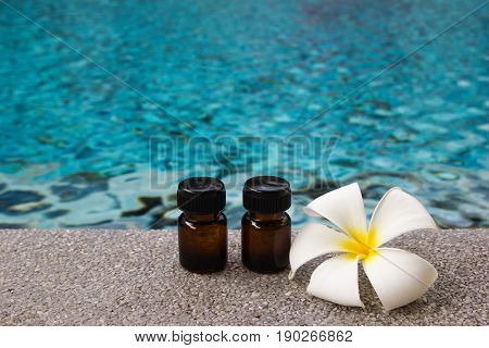 Two Bottles Of Aroma Essential Oil And Flower Of Frangipani (or Plumeria) On The Swimming Pool Backg