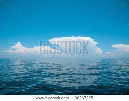 White clouds on blue sky over calm sea. Summer outdoor nature holiday serenity. South of Thailand Andaman sea Indian ocean.