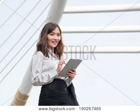 Lifestyle of a beautiful young Asian businesswoman holding digital tablet while standing in the city. Happy working girl smile and using internet outdoor over building background.