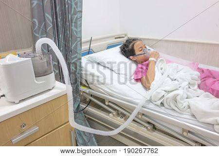 Ill young Asian girl sleeping on bed in hospital. Sick kid with Medical ultrasonic inhaler nebulizer nebular with mask. Respiratory medicine. Asthma breathing treatment. Asthmatic health equipment.