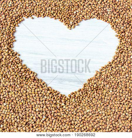Buckwheat Groats In A Heart Shaped Bowl On White Wooden Backgrou