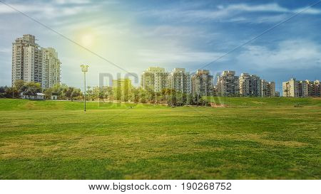 Rishon LeZion Israel-March 19 2016: View of big green field in front of Kiryat Rishon neighborhood under beautiful sky. There are some multi story residential buildings in the background. Bright sunny day. Horizontal shot.