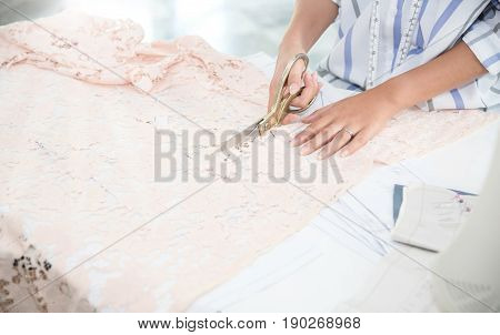 Close up of young Asian girl seamstress is cutting light pink Lace for a dress with scissors at home or studio. Tailor or dressmaker at work concept. Background copy space.