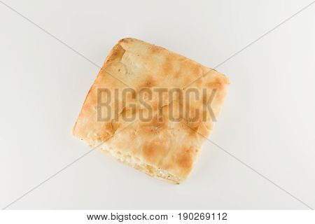 piece of khachapuri with cheese lies on a white table