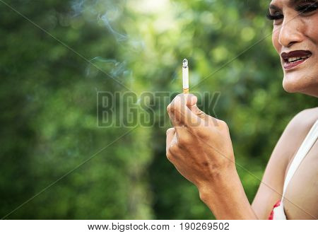 Close up of sad transwoman or transgender crying and holding cigarette in garden. People smoking and bad habits concept. Picture for World No Tobacco Day. Background or copy space.