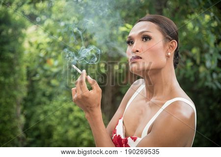 Portrait of Asian transwoman or transgender smoking cigarette in garden. People smoking and bad habits concept. Picture for World No Tobacco Day.