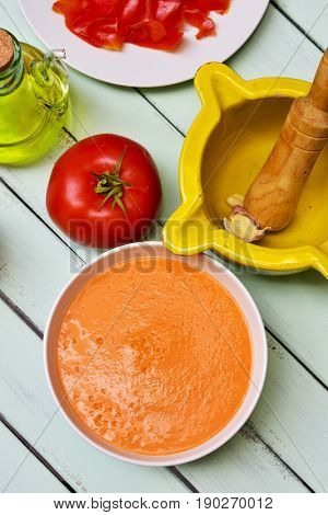 high-angle shot of a bowl with spanish salmorejo cordobes or porra antequerana, a cold tomato soup similar to gazpacho but thicker, and a tomato, a cruet with olive oil and a mortar on a table