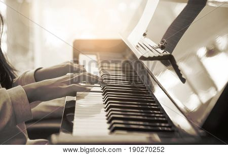 Close up of pre teen girl pianist practicing on an upright piano with classical music (soft focus and sepia tone)