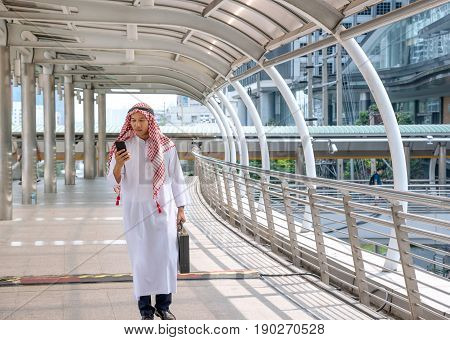 Arab saudi businessman in traditional clothing called kandura or dishdasha or thobe walking on walkway and checking mobile phone outdoor in the city with the background of urban landscape. Copy space.