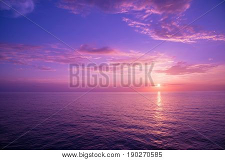 Background image of the ocean in summer time. Beautiful sunset sky over the sea at tropical beach in the evening with filter. copy space. South of Thailand Andaman sea Indian ocean.