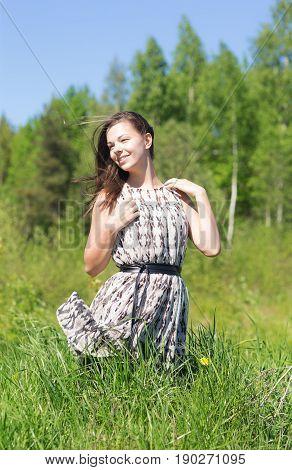 Cheerful girl in dress on summer grass