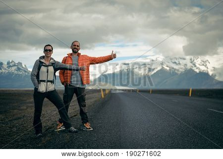 Travel hitchhiker couple on a road