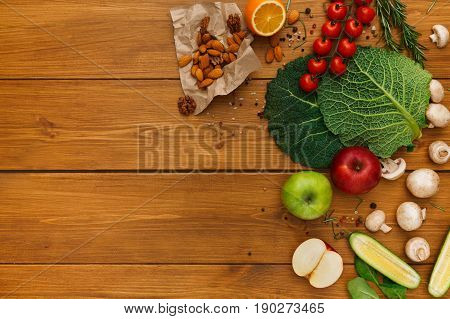 Healthy food, fresh vegetables on wood background with copy space, fruits and nuts. Healthy natural food on table with copy space. Cooking ingredients top view, mockup for recipe or menu
