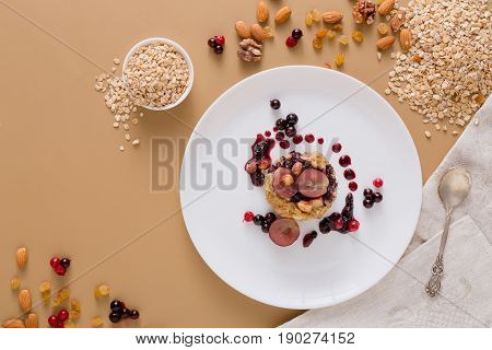 Healthy breakfast, dieting and detox concept - wholegrain fresh oatmeal porridge on plate with fruits, berries and nuts on beige background. Still life, top view