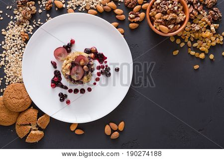 Healthy eating, dieting and detox concept - wholegrain fresh oatmeal porridge on plate with fruits, berries and nuts on beige background. Still life, top view