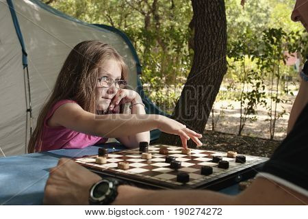 Little girl playing with her father draughts board outdoor (camping) in the sunny summer day. The touristic tent in background. Education summer active recreation and touristic concept.
