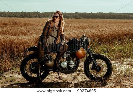 Woman rider with his vintage custom made cafe racer