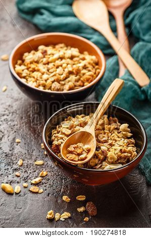 Delicious homemade granola or muesli in two ceramic bowls with wppden spoon on stone background.