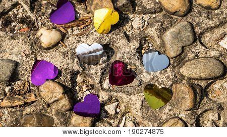 Color hearts confetti on the stone ground