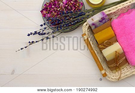 Spa and bath concept with natural soap, lavender and towel on wooden background