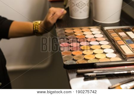 Cosmetic palette with the shadows lying on the table. Cosmetic makeup, women's beauty.