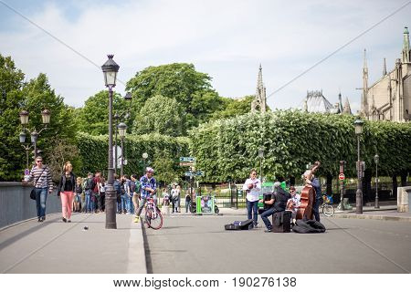 Paris, France - May 11, 2017: Group of street musicians performing on a bridge