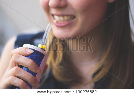 A woman using an oral irrigator in bathroom. Selective focus. poster