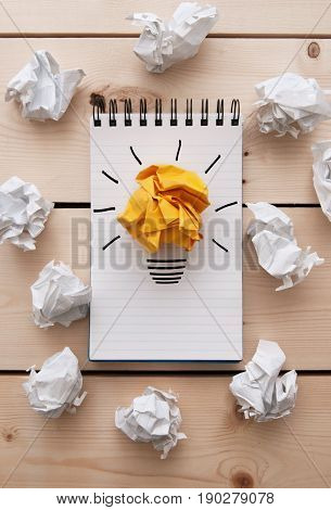 Bright paper light bulb on a notepad between crumpled pieces of paper