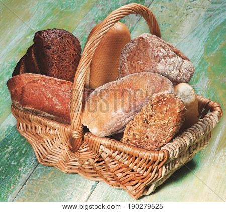 Various Buns Baguette Rye and Whole Wheat Bread in Wicker Basket closeup on Green Wooden background
