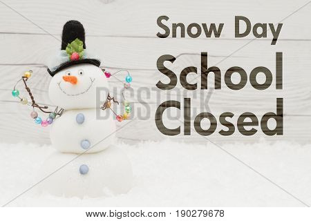 School canceled message A snowman with text Snow Day School Closed on weathered wood