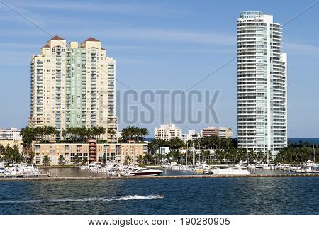 The jet ski passing by Miami South Beach marina and residential buildings (Florida).