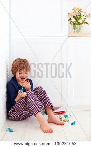 Sweet Tooth Kid Hiding In Kitchen Corner, Eating Candies