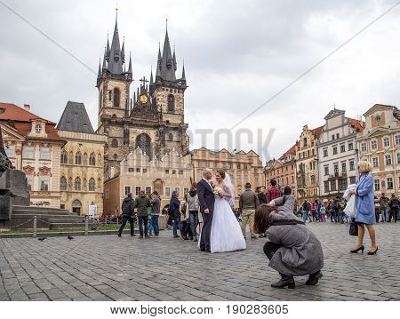 Prague, Czech Republic - March 17, 2017: A wedding couple getting photographed on the Old Town Suqare in the historic city centre