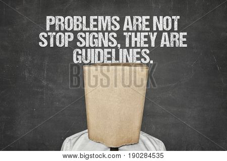 Businessman wearing paperbag in head under problems are not stop signs, they are guidelines text on blackboard