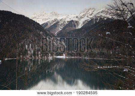 Mountain lake against the backdrop of snow-capped mountains. Rizza Abkhazia