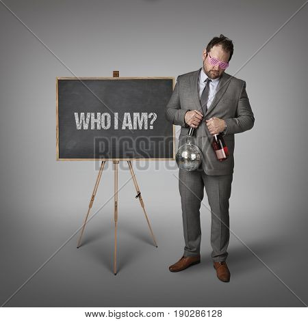 Who i am text on blackboard with businessman and key