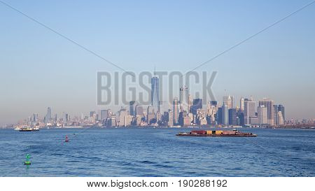New York, United States of America - November 18, 2016: A container ship  in front of the Lower Manhattan skyline